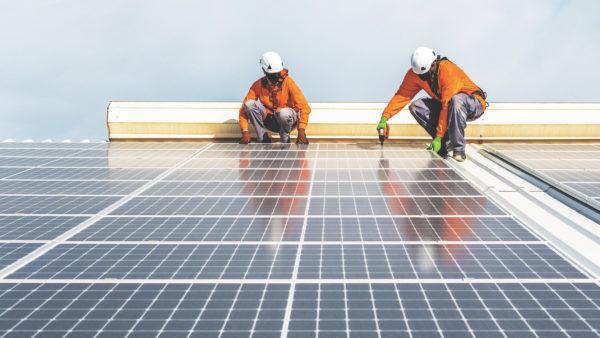 Unrecognizable solar panel technicians working a Spanish factory